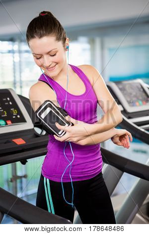 Fit woman using smartphone on treadmill at the gym