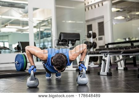 handsome man doing push ups with kettlebells