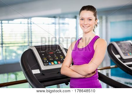 Smiling brunette with arms crossed standing on treadmill at the gym