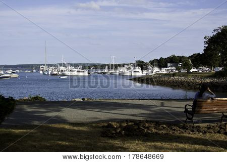 Plymouth, Massachusetts - September 11, 2014 - Wide shot boats and yachts in Plymouth Harbor with an woman sitting quietly on a park bench in Plymouth, Massachusetts on a bright sunny day with blue skies and clouds in September.