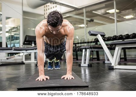 Shirtless man doing push up at the gym