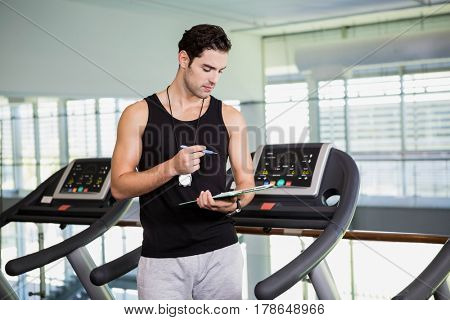Serious man on treadmill looking at clipboard at the gym