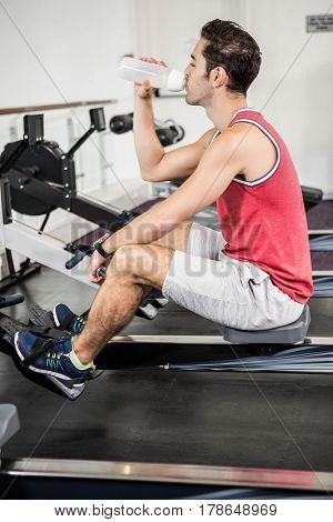 Muscular man on rowing machine drinking water in the gym