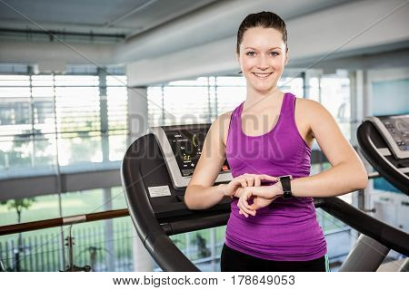 Smiling fit woman using smartwatch on treadmill in the gym