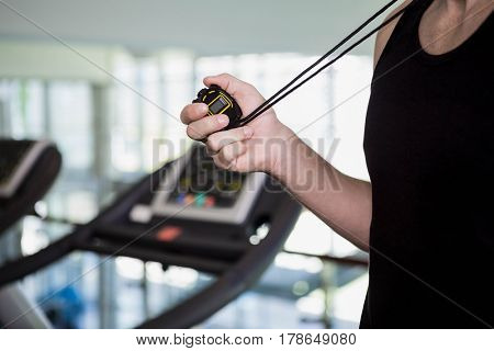 mid section of man holding stopwatch at the gym