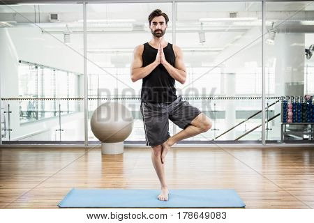 Handsome man doing yoga on mat in the studio