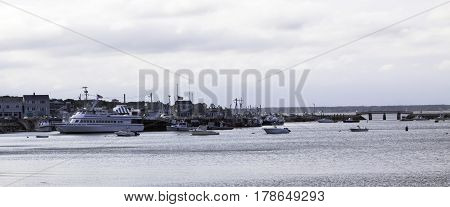 Plymouth, Massachusetts - September 11, 2014 - Wide view of fishing boats and a large tourist ship in Plymouth Harbor with part of the dock and buildings in view in Plymouth, Massachusetts on a bright sunny day with blue skies and clouds in September.
