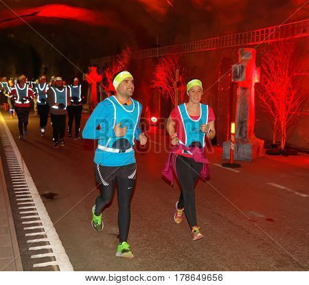 STOCKHOLM SWEDEN - MAR 25 2017: Smiling man and girl running in a tunnel with red light the Stockholm Tunnel Run Citybanan 2017. March 25 2017 in Stockholm Sweden