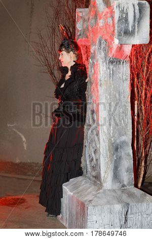 STOCKHOLM SWEDEN - MAR 25 2017: Woman in black dress looking like a vampire in red light leaning on a tomb stone in the Stockholm Tunnel Run in the Stockholm Tunnel Run Citybanan 2017. March 25 2017 in Stockholm Sweden