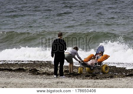 Barnstable, Massachusetts - September 12, 2014 -- Wide view of a happy family by the ocean playing with their handicapped child who is in a special wheeled flotation chair and is smiling brightly at Sandy Neck Beach, Barnstable, Cape Cod, Massachusetts on