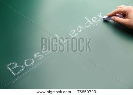 Female hand with chalk and words BOSS VS LEADER on chalkboard