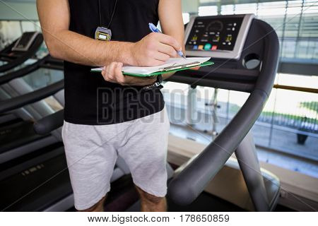 Mid section of man on treadmill writing on clipboard at the gym