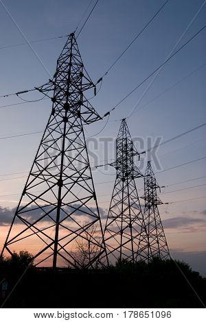 Electric pylons with cables on sunset background