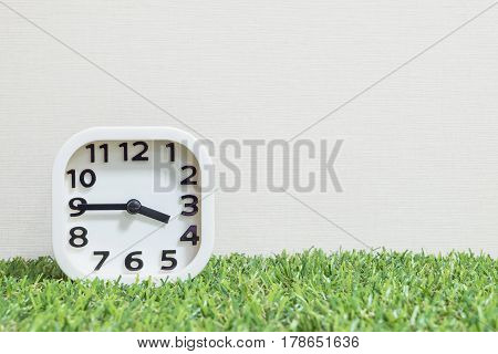 Closeup white clock for decorate show a quarter to four o'clock or 3:45 p.m. on green artificial grass floor and cream wallpaper textured background with copy space