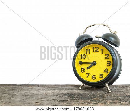 Closeup black and yellow alarm clock for decorate show a quarter to eight o'clock or 7:45 a.m. on old brown wood desk isolated on white background with copy space