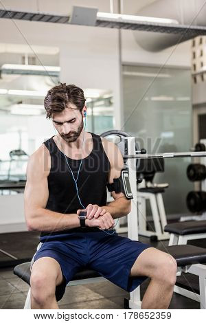 Muscular man sitting on barbell bench and using smartwatch at the gym