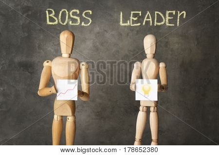 Boss vs leader concept. Wooden figures on grey background