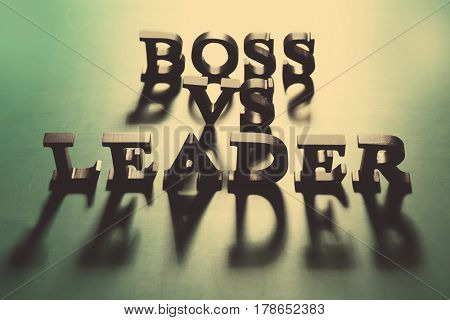 Boss vs Leader phrase made of black letters on green background