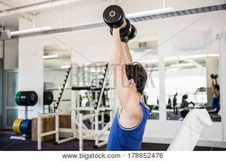 Muscular man lifting dumbbells on bench at the gym