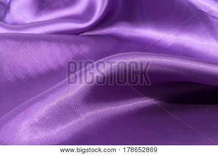 Silk background texture of violet shiny fabric close up
