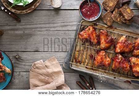 Chicken wings in cranberry sauce on rustic wooden table with copy space top view. Tasty and healthy food