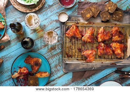 Chicken wings in cranberry sauce with lager beer on wooden table top view. Rustic style