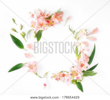 Frame with alstroemeria leaves and petals on white background. Flat lay top view
