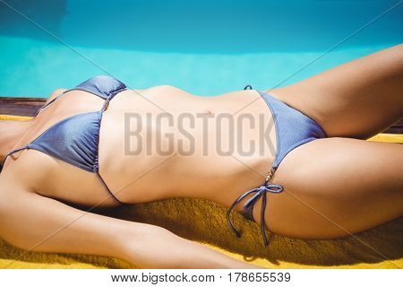 Fit woman lying on towel poolside