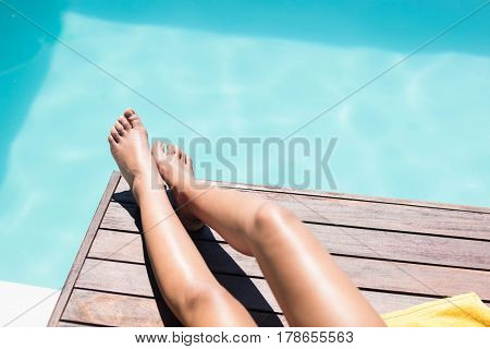 Feet of woman on pool edge in a sunny day
