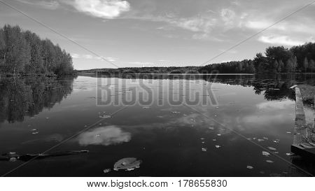 Black-and-white photograph. A beautiful large tranquil lake. It reflects the forest and clouds. Visible pier and lilies floating in a lake