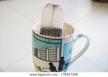 Closeup teabag put in white and blue ceramic mug