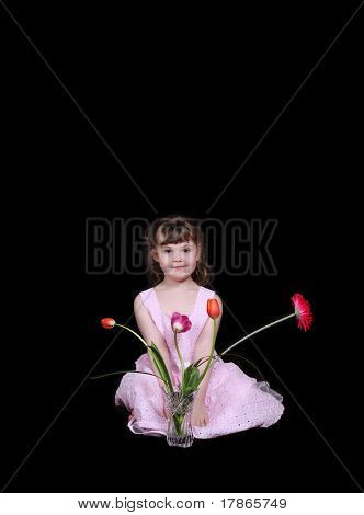 sweet little girl in dress sitting with vase of bright tulips isolated on black poster