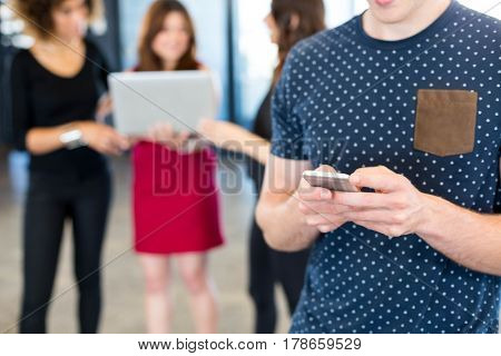 Man text messaging on smartphone while her colleagues standing behind her in office