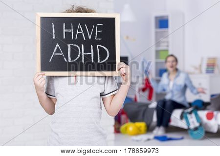 Boy holding blackboard and admitting suffering from ADHD