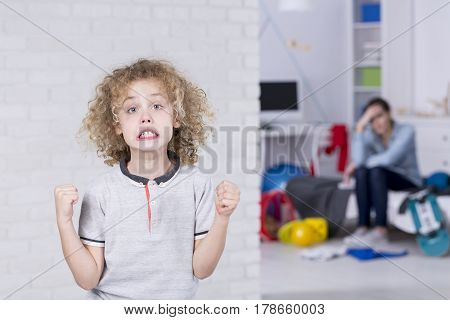 Young boy with bad mood clenching his fists