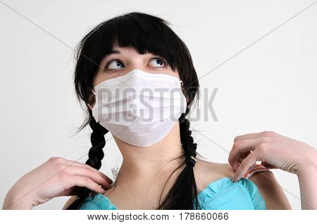 close-up portrait of young woman in protective medical mask on white background looking up