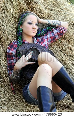 young tattooed stylish woman with dreadlocks in cowgirl stylerelaxing on haystack