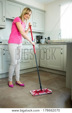 Pretty blonde woman swiping the kitchen floor with a mop