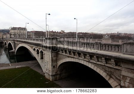 Lyon, France - December 20, 2016: Quay of the river Rhone and Wilson Bridge. On the background Basilica of Notre-Dame de Fourviere in December 20 in Lyon, France
