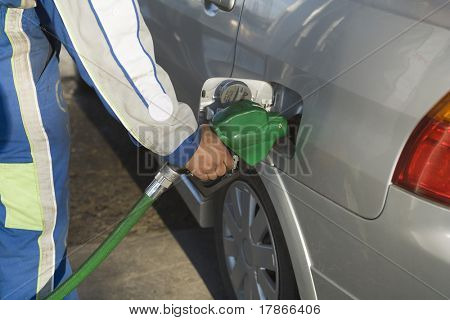 Service station employee pumping gasoline