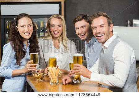 Attractive friends smiling at camera in a bar with beers in hand
