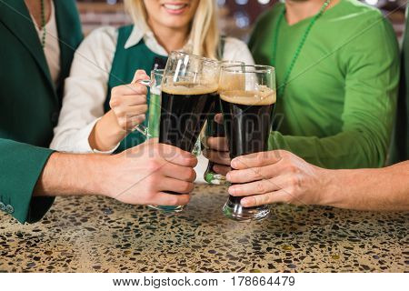 Men toasting with normal beers woman with a green beer