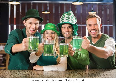 Friends wearing St. Patricks day associated clothes toasting in a bar