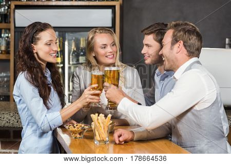 Attractive friends toasting with pints of beer at a bar