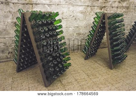 Sparkling wine is aged in bottles on wooden stands in a cellar