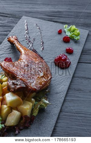 Roasted duck leg closeup served with apples and cherry sauce. Restaurant food on black slate plate at wood table. Vertical