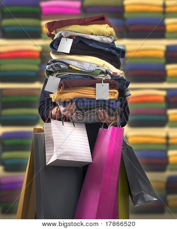 Woman carrying bags and a pile of clothes with tags
