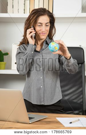 Businesswoman Looking World Globe And Talking On Phone