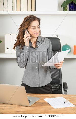 Businesswoman Talking On Phone With Paper In Hand