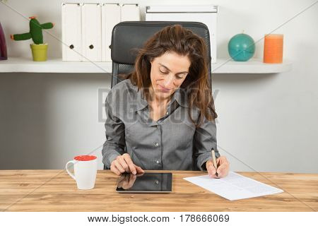 Businesswoman With Tablet Writing In Paper